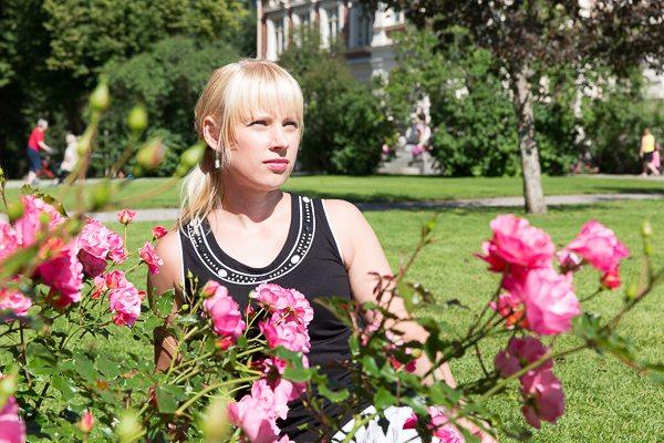 Henkilö ruusujen keskellä; Kuvattava erottuu taustasta.